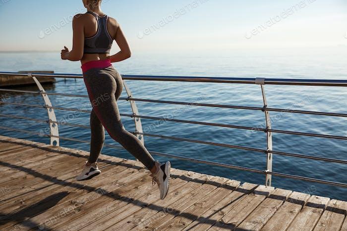 Recortado tiro trasero de mujer fitness jogging en un muelle, entrenamiento solo