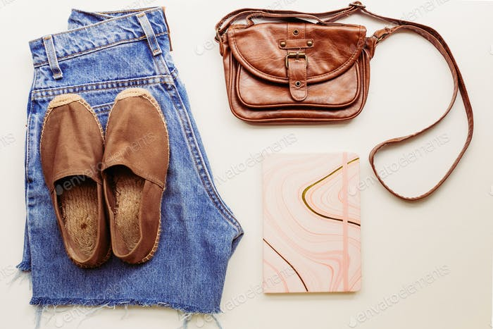 Ideal clothes for summer outfits: a shirt, jeans, a bag, shoes. View from above.