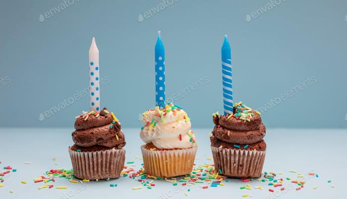Birthday cupcakes with candles on blue pastel background, copy space.