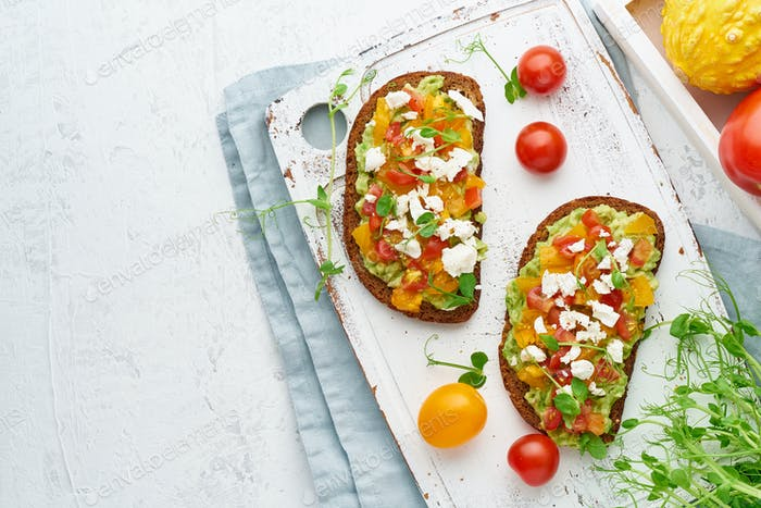 avocado toast with feta and tomatoes, smorrebrod with ricotta, top view with copy space