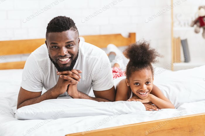 African father and daughter lying on bed on bed together