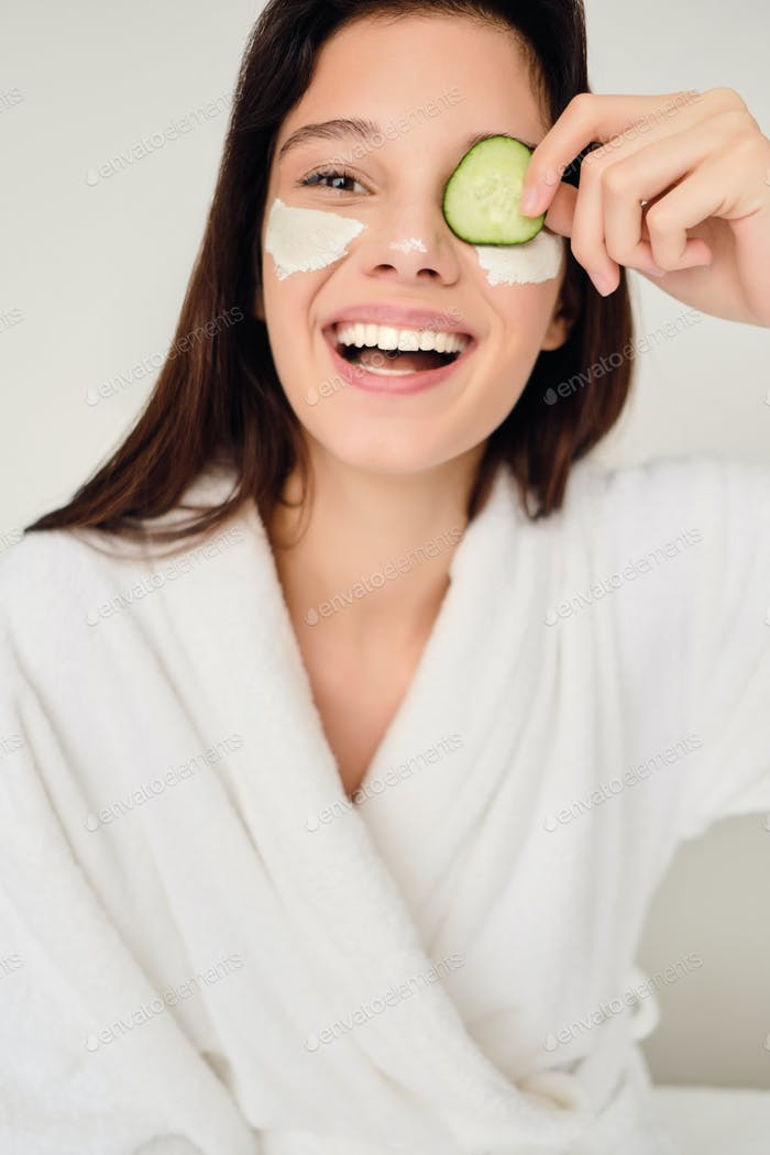 Young cheerful woman in bathrobe with cosmetic mask on face happily looking in camera