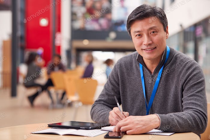 Portrait Of Mature Male Teacher Or Student With Digital Tablet Working At Table In College Hall