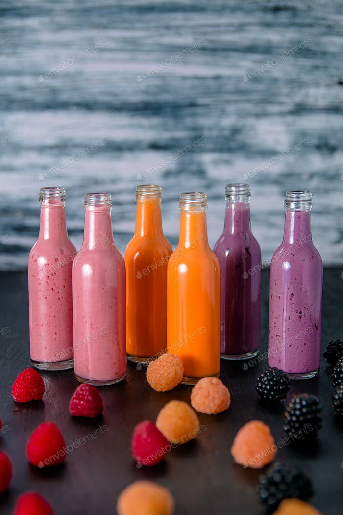 Six bottles with smoothies and raspberry, red, yellow, blackberry. Milk shake