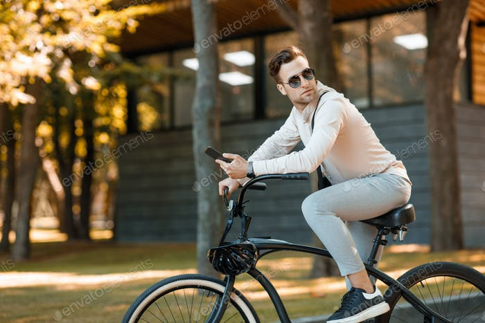 Businessman riding on bicycle. Guy in sunglasses and smartphone in the park