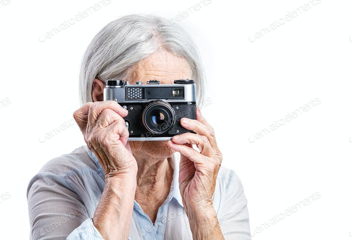 Senior woman shooting with a retro camera over white