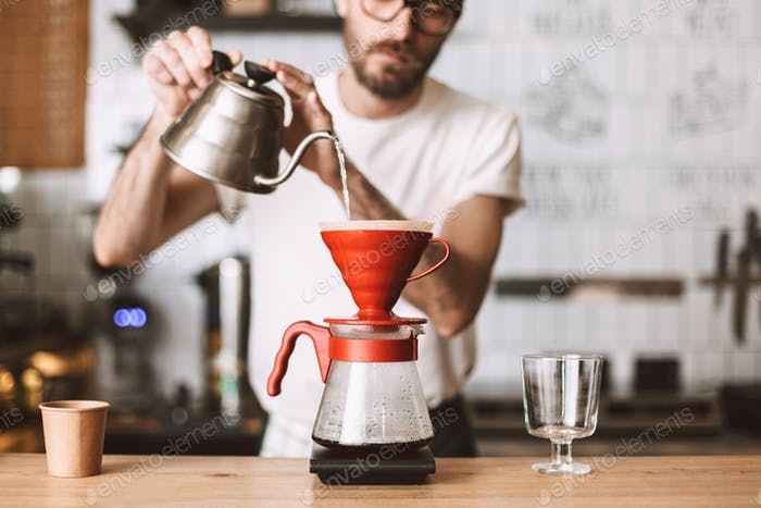 Close up photo of barista standing at counter and preparing pour over coffee in cafe