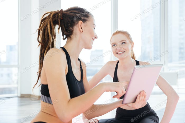 Two cheerful sportswomen using tablet together