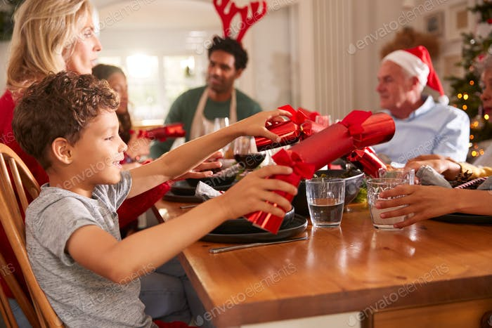 Multi Generation Family Pulling Christmas Crackers As They Sit For Meal At Table