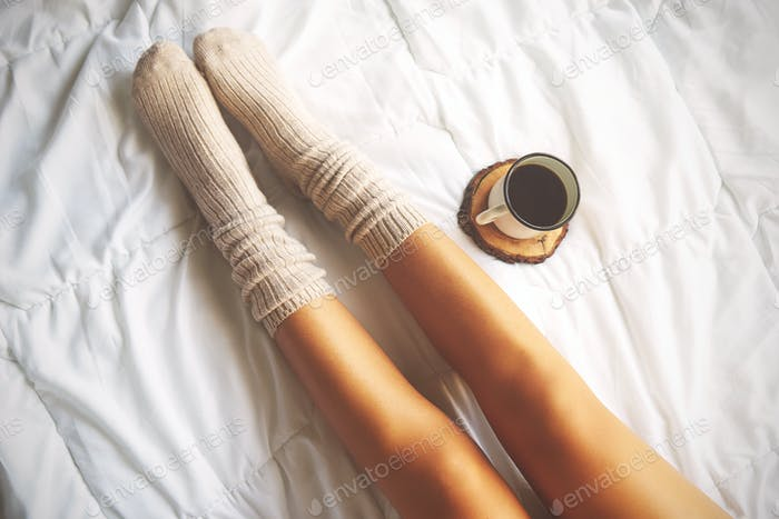 Soft photo of woman on the bed with cup of coffee, top view