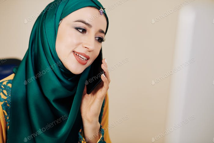 Muslim businesswoman making phone call
