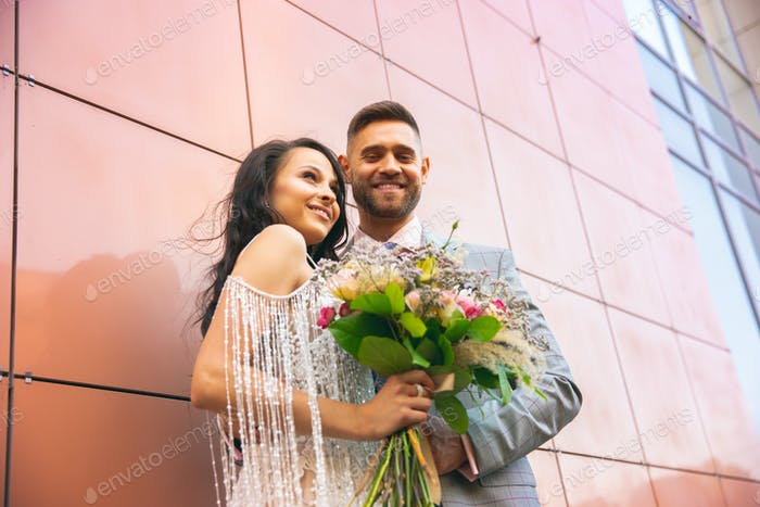 Caucasian romantic young couple celebrating their marriage in city