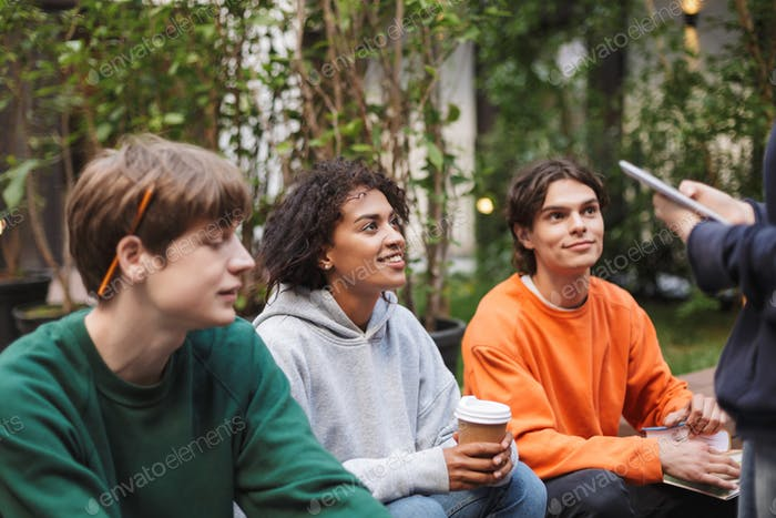 Group of young students sitting with coffee to go and books in hands while studying together