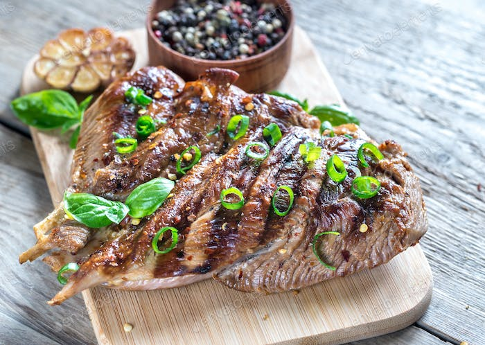 Grilled turkey with green scallion on the wooden board