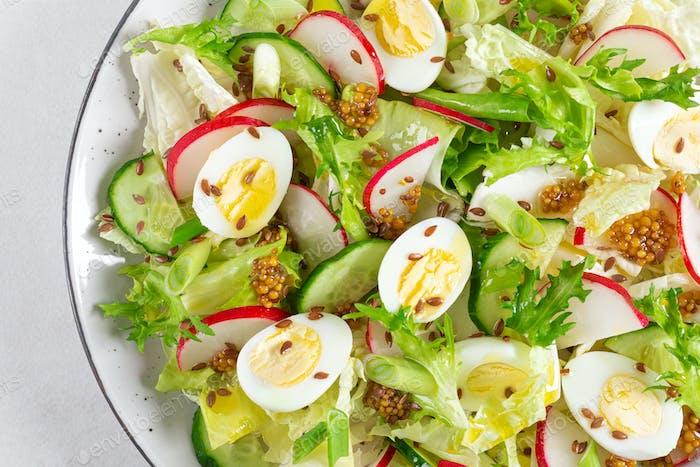 Frischer Gemüsesalat mit Gurken, Rettich, Salat und gekochten Eiern