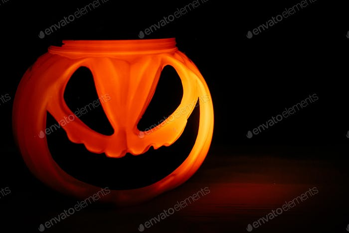 Halloween pumpkin with scary glowing face on black background isolated