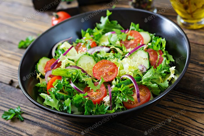 Salad from tomatoes, cucumber, red onions and lettuce leaves.
