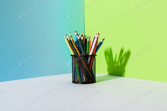 Pencil Holder With Colored Pencils on Blue, Green And White Background