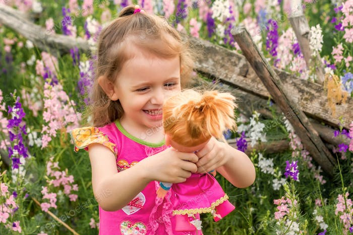 Cute smiling baby girl in bright dress plays with doll outdoors in green field