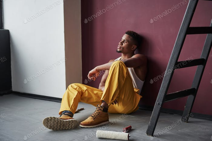 Thoughtful look. Young african american worker in the yellow uniform have some job