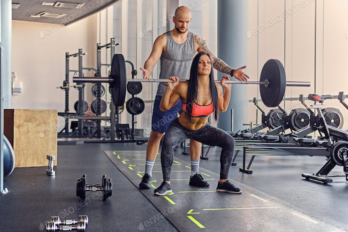 A man learning a woman doing squats.