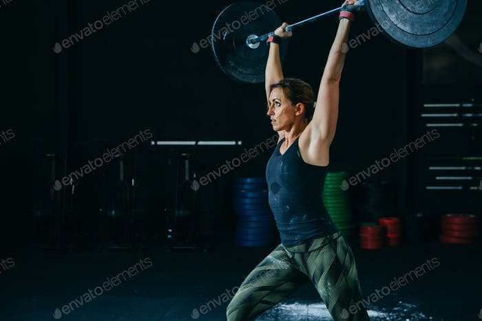 Woman does jerk with barbell