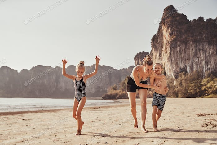 Laughing Mother and her adorable children running along a beach