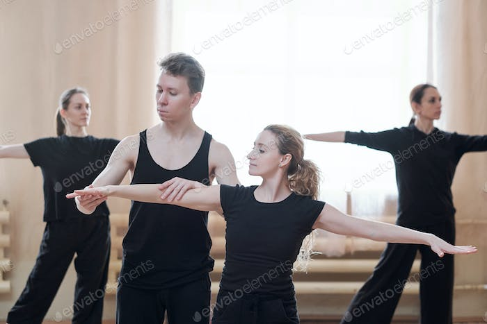 Young male instructor helping one of females with outstretched arms