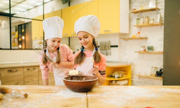 Little girls cooks in caps adds butter to the bowl