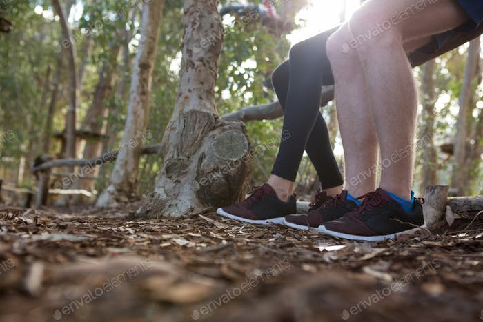 Legs of man and woman sitting on log of wood in the forest