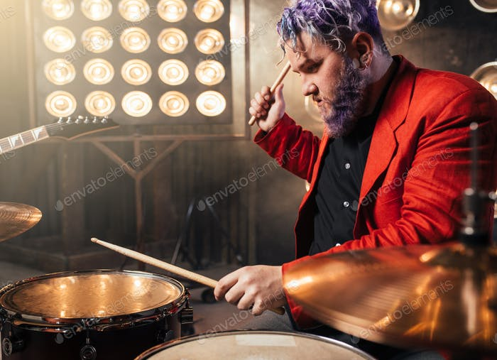 Bearded drummer in red suit, performing on stage
