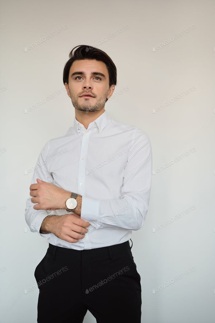 Young handsome brunette man in white shirt and black trousers with watch dreamily looking aside