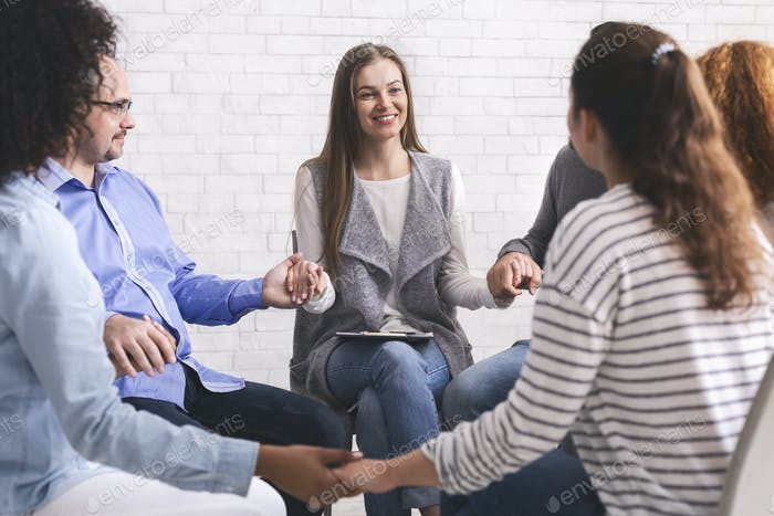 Group of addicted people holding hands, sitting in circle of trust