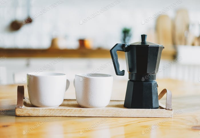 Two white ceramic mugs and geyser coffee maker on wooden tray on kitchen table