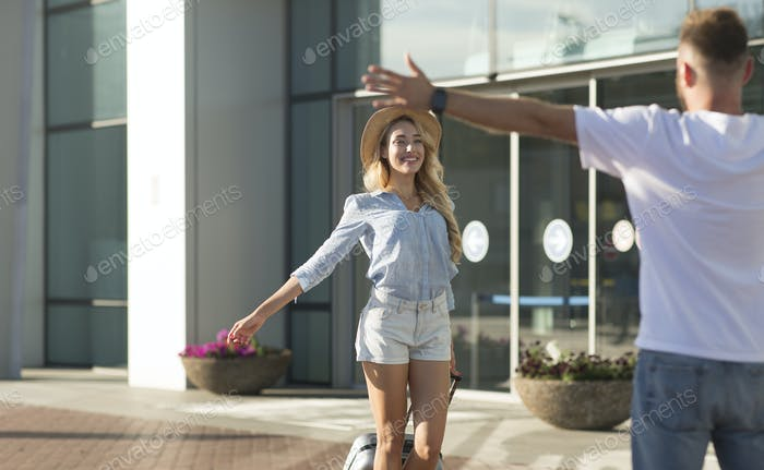 Boyfriend picking up his girlfriend near airport building