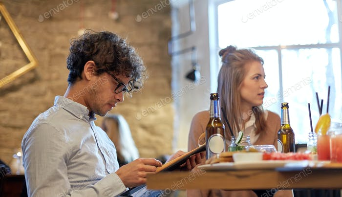 happy friends looking to menu at restaurant