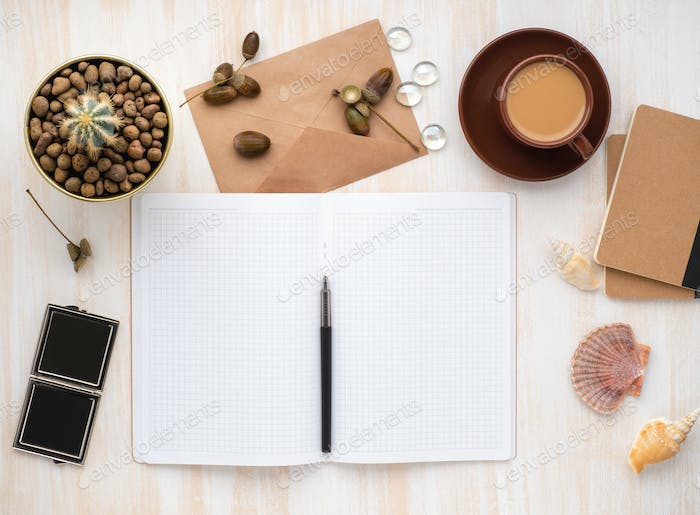 white open notepad, kraft envelope, cup of coffee and cactus in pot lying on beige wooden desk