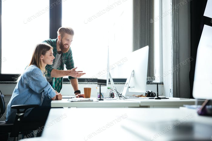 Two young smiling colleagues work in office
