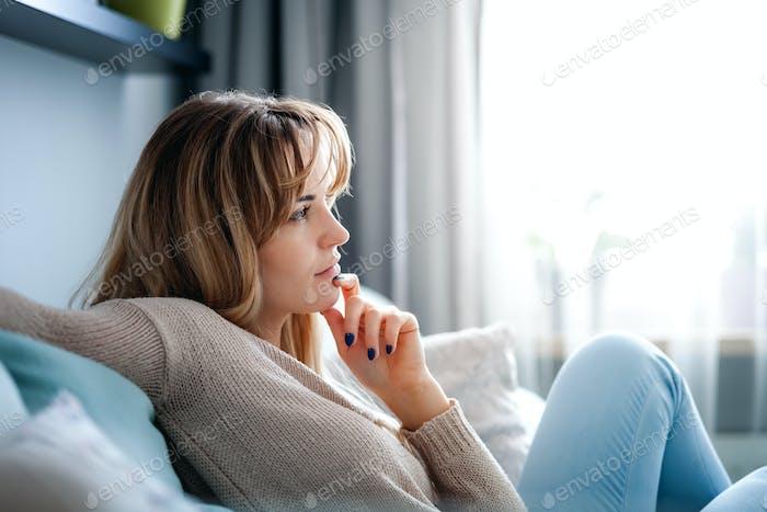 Frau zu Hause tief in Gedanken denken und planen