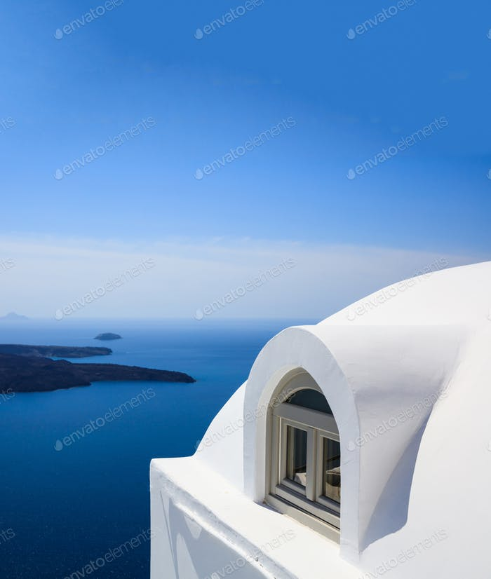 Whitewashed house detail in Santorini island, Cyclades, Greece. Aegean sea background