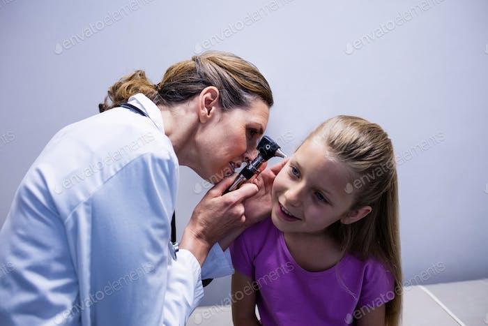 Ärztin Untersuchung Patientenohr mit Otoskop
