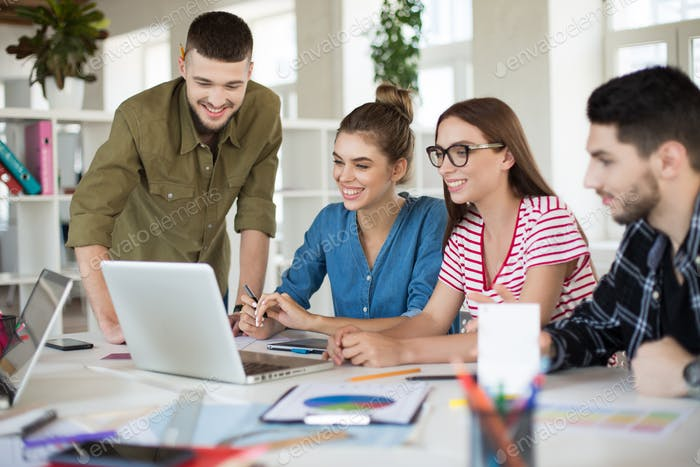 Young positive business people joyfully working on laptop togeth