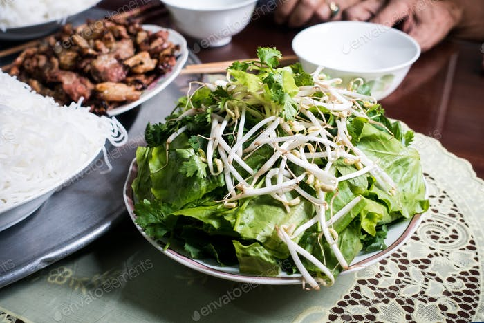 Bowl of fresh herbs and bean sprouts on a table
