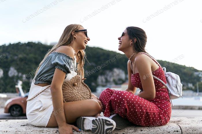 Молодые подружки, наслаждающиеся сидячие