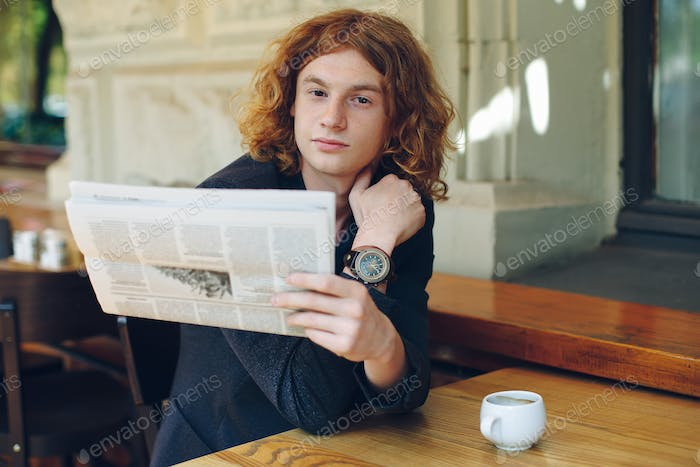 Young man reading a newspaper in the morning
