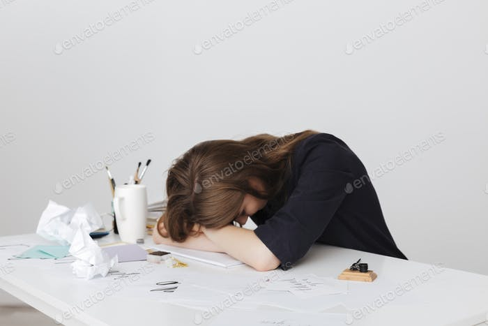 Photo of tired lady sitting at the white desk and sleeping while leaning head on her hands isolated