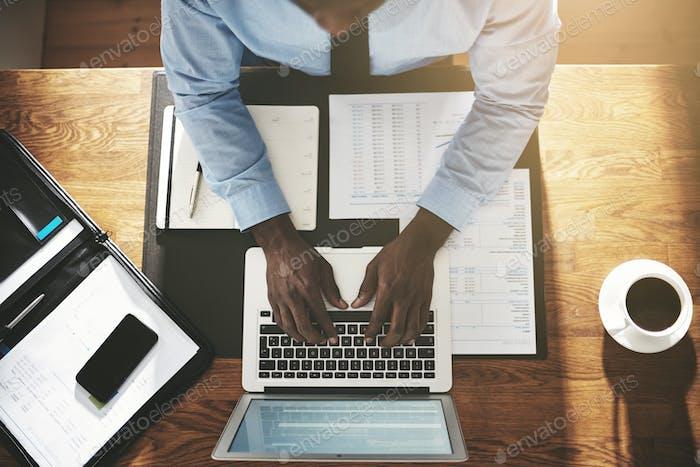 Executive beschäftigt Arbeit an einem Laptop an seinem Schreibtisch