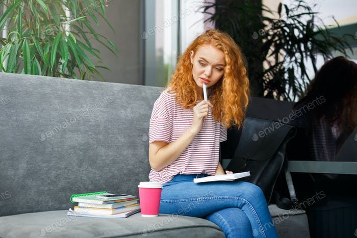 Young pensive redhead student girl with notepad sitting on grey couch