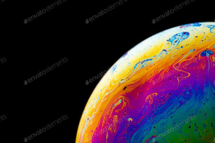 Rainbow soap bubble on a dark background