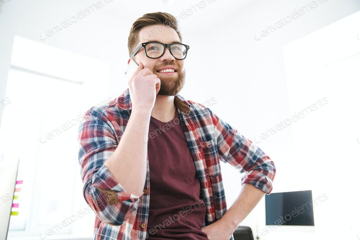 Cheerful young bearded man in glasses talking on mobile phone